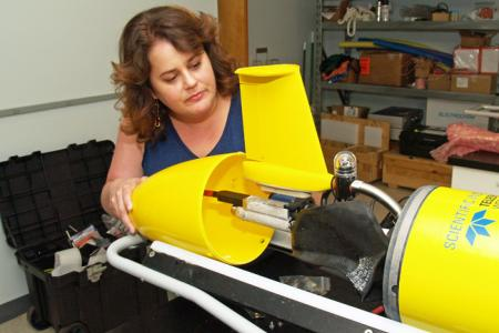 UGA Skidaway Institute researcher Catherine Edwards examines the tail assembly of a glider.